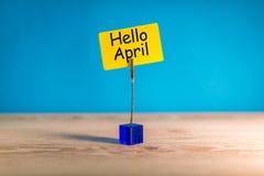 Bonjour salutation d'avril écrite sur l'étiquette jaune au bureau en bois photo stock
