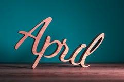 Bonjour texe en bois d'avril écrit sur le fond foncé Concept de printemps photographie stock libre de droits