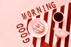 Bonjour textes, café, beignet, a monté fleur sur la serviette et sur le fond rose Lieu de travail élégant de concept étendu par a images stock