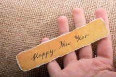 Bonne année écrite sur un papier déchiré à disposition Image libre de droits