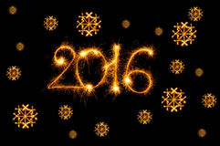 Bonne année - 2016 avec des flocons de neige faits par des cierges magiques sur le noir Photo stock