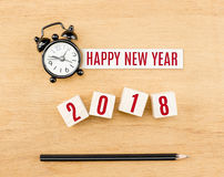 Bonne année 2018 avec le cube en réveil et en bois sur l'étiquette de bureau Photos libres de droits