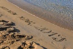 Bonne année 2019 d'inscription sur le sable par la mer photographie stock libre de droits