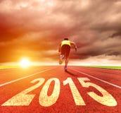 Bonne année 2015 jeune homme courant avec le lever de soleil Images stock
