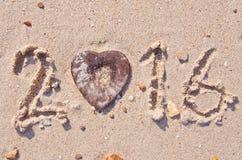 Bonne année 2016 sur la texture de fond de sable et la coquille en forme de coeur de noix de coco Images libres de droits