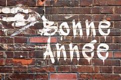Bonne annee som betyder lyckligt nytt år i franskt, på en wal tegelsten Fotografering för Bildbyråer