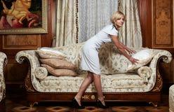 Bonne attirante effectuant un sofa dans l'hôtel de luxe Photo libre de droits