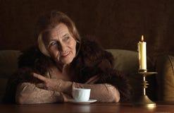 Bonne dame s'asseyant sur un sofa Photo stock