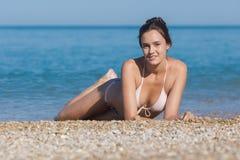 Bonne jeune femme sur le bord de la mer de caillou Photos libres de droits
