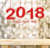 2018 bonnes années accrochant au-dessus du dessus de table en bois simple avec la tache floue Images stock