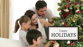 Bonnes fêtes contre la famille décorez l'arbre de Noël banque de vidéos