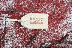 Bonnes fêtes l'étiquette de cadeau sur le style rouge de vintage a réutilisé le bois Image libre de droits