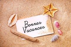 Bonnes-vacances (glücklichen Feiertag bedeutend) auf einer Anmerkung über weißen Strandsand Lizenzfreies Stockfoto