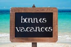Bonnes-vacances (glücklichen Feiertag bedeutend) geschrieben auf ein hölzernes vintag Kreidebrett Lizenzfreie Stockbilder