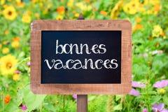 Bonnes-vacances (glücklichen Feiertag bedeutend) geschrieben auf eine Holzrahmentafel der Weinlese Lizenzfreie Stockbilder