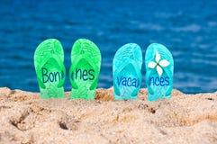 Bonnes-vacances (glücklichen Feiertag bedeutend) geschrieben auf Flipflops Stockfotografie