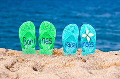 Bonnes vacances (meaning happy holiday) written on flip flops. On a beach stock photography