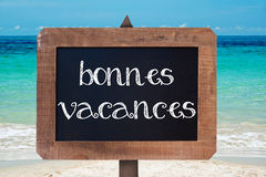 Bonnes vacances (meaning happy holiday) written on a wooden vintag chalk board Royalty Free Stock Images