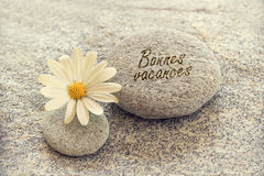Bonnes vacances (meaning happy holiday) written on zen pebbles Royalty Free Stock Images