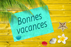Bonnes vacances (meaning happy summer). Written on a paper on colorful wood background with palm trees and sea shells royalty free stock photo