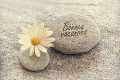 Bonnesvacances die (gelukkige die vakantie betekenen) op zenkiezelstenen wordt geschreven Royalty-vrije Stock Afbeeldingen