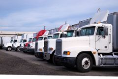 Big rig semi trucks different makes and models standing in row o. Bonnet semi trucks of different colors, models and designs for different uses for the purpose Stock Images