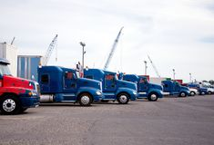 Big rigs semi trucks standing in row on huge parking lot at indu Royalty Free Stock Photos
