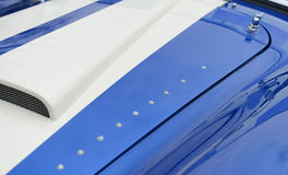 Bonnet of sports car. Bonnet or hood of classic blue and white sports car Stock Photos