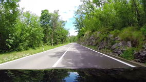 Bonnet-view footage of a car going down the winding road stock video footage