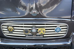 Bonnett and grille vintage car. Close-up bonnet and grilles of vintage grey morris car with five vintage motoring badges aa and rac badges along with racing Royalty Free Stock Photos
