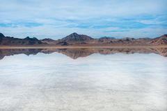 Bonneville Salt Flats, Tooele County, Utah, United States. Crystal clear water with mountains and blue, cloudy sky. Bonneville Salt Flats, Tooele County, Utah Royalty Free Stock Photo