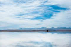 Bonneville Salt Flats, Tooele County, Utah, United States. Reflection of blue, cloudy sky in water with mountains in background. Bonneville Salt Flats, Tooele Royalty Free Stock Image
