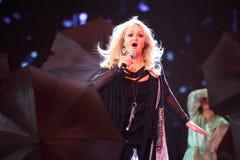 Bonnie Tyler zingt op scène met dansers stock afbeelding