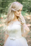 Bonny blonde bride touches her hair delicately. While standing in the forest Stock Photos