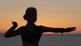 Bonny girl dancing oriental dance at sunset stock video
