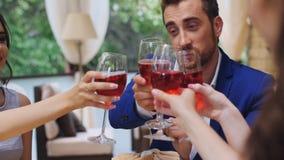 Bons amigos para o jantar ou o almoço em um restaurante fino, vidros do tinido video estoque