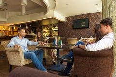 Bons amis dans le restaurant à manger, boire Image stock