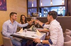 Bons amis dans les verres de tintement de restaurant Photos stock