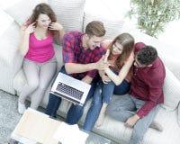 Bons amis s'asseyant sur le divan et se donnant cinq Image libre de droits