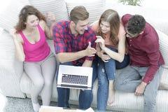 Bons amis s'asseyant sur le divan et se donnant cinq Photographie stock libre de droits