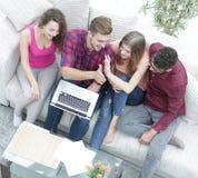 Bons amis s'asseyant sur le divan et se donnant cinq Photo libre de droits