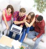Bons amis s'asseyant sur le divan et se donnant cinq Photos libres de droits