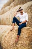 Bons olhares do homem novo nos óculos de sol na palha Imagem de Stock Royalty Free