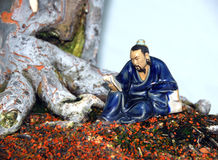 Bonsai decoration. Picture of a bonsai tree with a small statue besides it Stock Photo