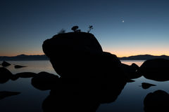 Bonsai Rock, Lake Tahoe, Sunset. Sunset with crescent moon at Bonsai Rock on Lake Tahoe near border of California and Nevada Royalty Free Stock Photography