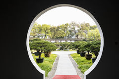 Bonsai and Round gate in Duojing garden Royalty Free Stock Photos