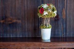 Bonsaivasen på hyllaen trähylla blommar i inre royaltyfri foto