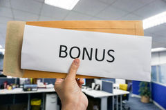 Bonus from the envelope. Concept of bonus by pulling paper of bonus from the envelope stock images