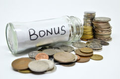 Bonus lable in a glass jar with coins spilling out Stock Photography