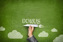 Bonus word on blackboard. With businessman hand holding paper plane stock photo
